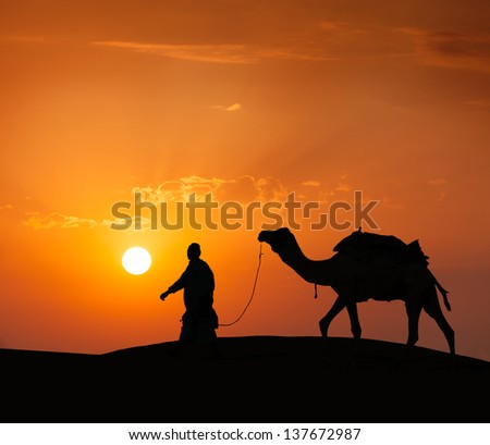 Rajasthan travel background - indian cameleer (camel driver) with camel silhouette in dunes of Thar desert on sunset. Jaisalmer, Rajasthan, India - stock photo