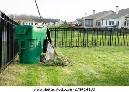 Raking lawn clippings on a neat upmarket suburban housing estate with a heap of grass cutting alongside a rake leaning on a green plastic bin for composting organic waste - stock photo