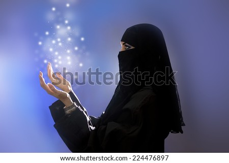 Ramadan: Beautiful young muslim woman with hijab and jewelry praying, spirituality light - stock photo