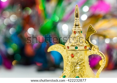 Ramadan, Eid Concept - Golden arabic coffee pot in colorful out of focus background - stock photo