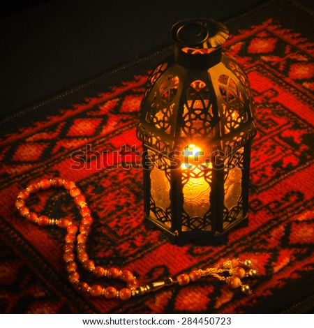 Ramadan greeting card background. An illuminated lamp on bright red carpet background. - stock photo