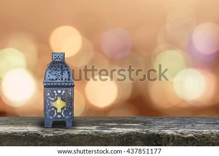 Ramadan kareem lantern on grunge antique wood table floor w/ blur festive colorful gold candle light illumination pattern background: Islamic calendar muslims religious fasting month worldwide concept - stock photo