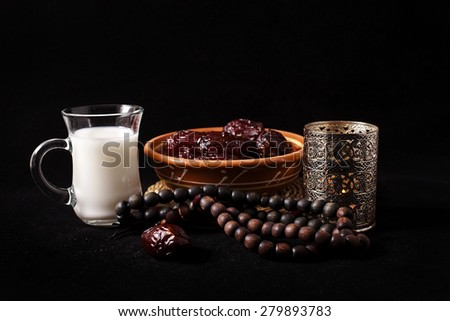 Ramadan lamp and dates with cup of water, still life on black background  - stock photo