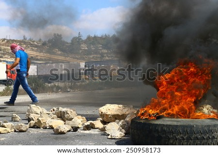 RAMALLAH, PALESTINE - AUGUST 9, 2014: A masked Palestinian strides past a burning tire during clashes with Israeli soldiers at Ofer Prison in Ramallah, Palestine on August 9, 2014. - stock photo