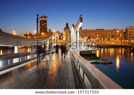 Rambla de Mar wooden walkway over Port Vell in the city of Barcelona at night in Catalonia, Spain. - stock photo