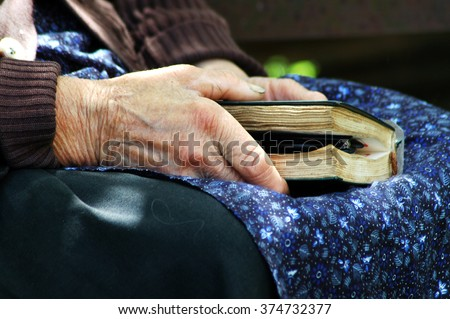 RAMETI, ROMANIA - JUNE 6, 2010: Elder woman holding a Bible in her hand. The older generations in the rural areas of Romania are very religious - stock photo