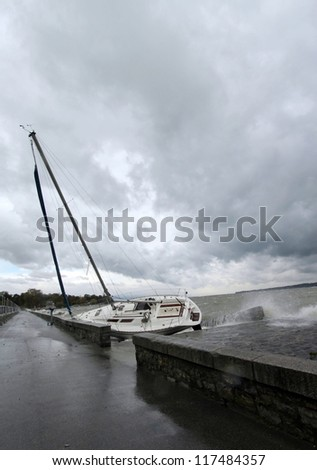 Ran aground boat during big storm by cloudy and rainy day in Geneva, Switzerland - stock photo