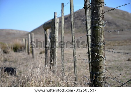ranch fence post with barbed wire - stock photo