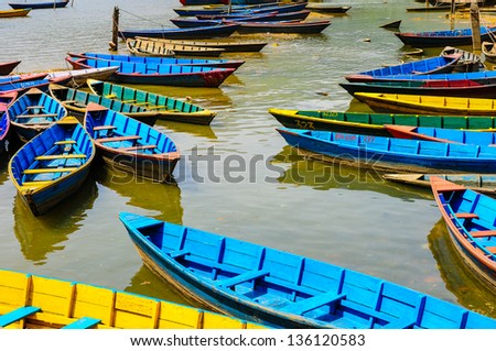 Random collection of colorful lake boats moored on the shore of Phewa Lake, Pokhara Nepal - stock photo