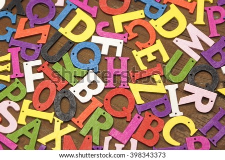 Random English Wooden Multicolored Letters On the Brown Wood Background, Close Up, Top View, Horizontal Image - stock photo