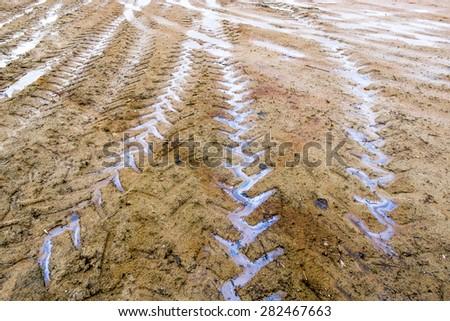 Random truck tire Marks on the yellow sand. - stock photo