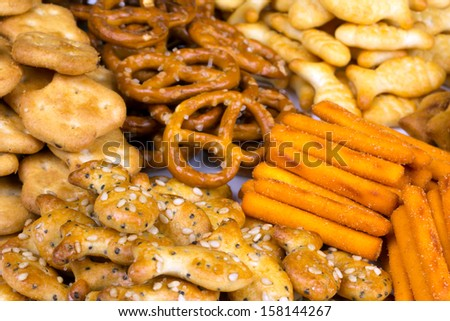 range of salty snacks lying on a white plate - stock photo