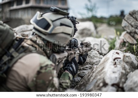 ranger on battle field, aiming on enemy, view from behind - stock photo