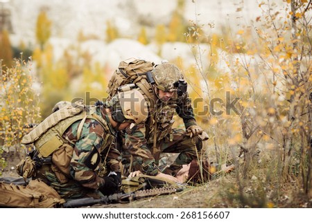 Rangers team medic assists wounded soldier - stock photo