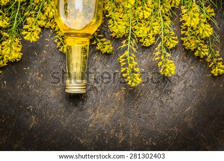 Rape oil and Rape blossoms on dark rustic wooden background, top view, place for text - stock photo