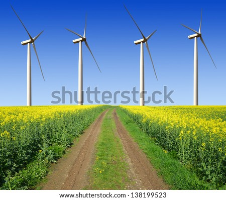 rapeseed field with wind turbines against the blue sky - stock photo