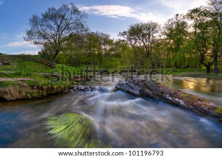 Rapid current on the spring river, around the wood, long exposure - stock photo