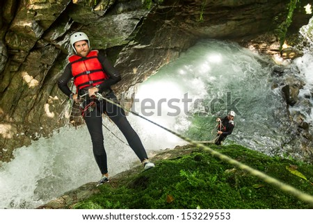 Rappelling into a waterfall, specialized guide in the background. - stock photo