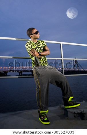 rapper on quay with bottle of champagne in the bright of the moon - stock photo