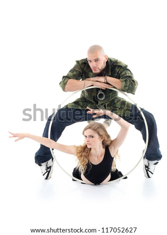 Rapper stands over girl and puts hands on hoop and gymnast girl lies on floor in hoop and depicts something by hands isolated on white background. - stock photo