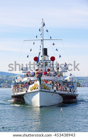 """RAPPERSWIL, SWITZERLAND - AUGUST 17, 2014: Historical steam boat """"Stadt Rapperswil"""" arriving to pier on lake Zurich.Steamboat cruises on the lakes is popluar tourist attaraction of Switzerland - stock photo"""