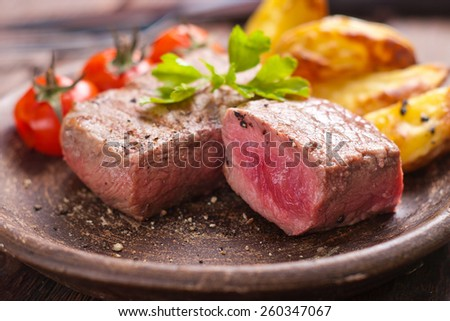 Rare beef steak on rustic plate witch baked potatoes and tomatoes. - stock photo
