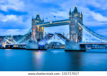 Rare image of Tower Bridge in London fully open at night - stock photo