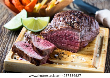 Rare roast beef sirloin with french fries and slices baked pumpkin chips on cutting board - stock photo