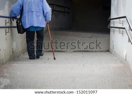 Rare view of senior coming down stairs - stock photo