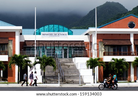 RAROTONGA - SEP 16:Cook Islanders pass by the Cook Islands Minister of Justice building on Sep 16 2013.Cook Islands legal system is based on New Zealand law and English common law. - stock photo