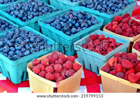 raspberries and blueberries in square produce boxes at the farmer's market - stock photo