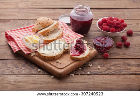 Raspberries berries, raspberries jam, butter and bread on wooden table. Breakfast with fruits top view horizontally. Overhead view on healthy breakfast with strawberry jam. Macro shot selective focus - stock photo