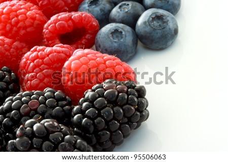 Raspberries, Blueberries and Blackberries on White Ceramic plate - stock photo