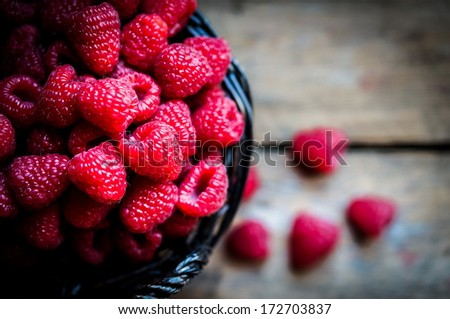 Raspberries in a basket on rustic wooden background - stock photo