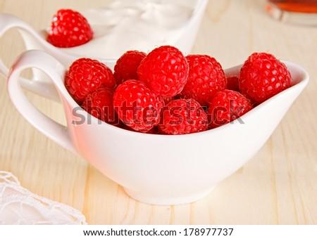 Raspberries  in  the white salad-bowl served with yogurt. - stock photo