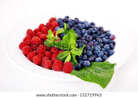 Raspberry and blueberry with mint on white plate - stock photo
