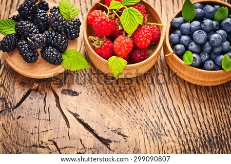 Raspberry Blueberry and Blackberry on a wood background - stock photo