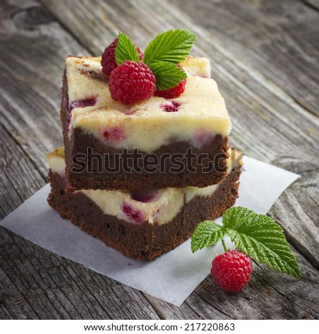 raspberry cheesecake brownies on a rustic wooden background, square image - stock photo