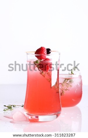 raspberry cocktail in a glass with fresh berry and thyme