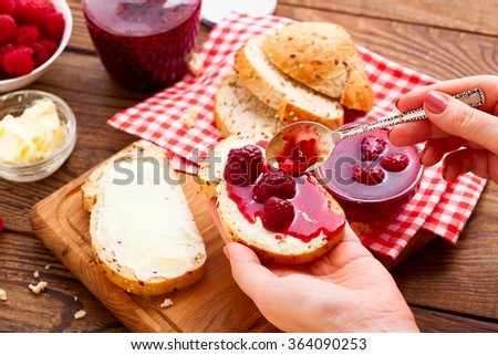 Raspberry jam to smear. Raspberry jam Woman plaster bread and butter. Jars of raspberry jam with berries on tray close up - stock photo