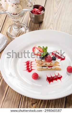 Raspberry mille feuille dessert on wooden background - stock photo