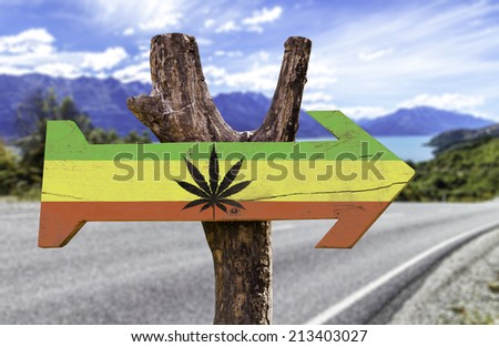 Rasta Flag With Marijuana Leaf wooden sign with a street background  - stock photo