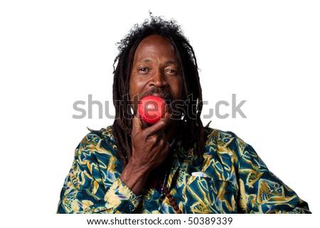 Rasta man eating an organic apple, studio shot - stock photo