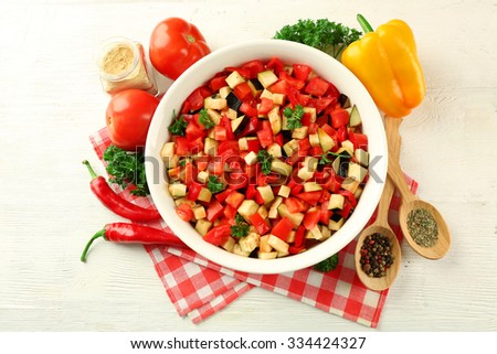 Ratatouille before cooking and ingredients, on wooden background - stock photo