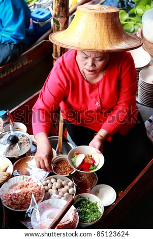 RATCHABURI, THAILAND - FEB 13: A woman serves Thai food at Damnoen Saduak floating market on February 13, 2011 in Ratchaburi, Thailand. Its popular for traditional style food and old Thai culture. - stock photo