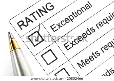 "Rating ticked in the ""exceptional"" box.  With silver and gold ballpoint pen. - stock photo"