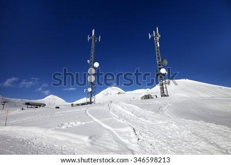 Ratrac ski road and satellite dishes at nice sun day. Caucasus Mountains. Georgia, region Gudauri. Wide angle view. - stock photo