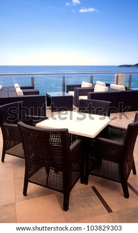 Rattan armchairs on the terrace lounge with sea view in a luxury resort . - stock photo
