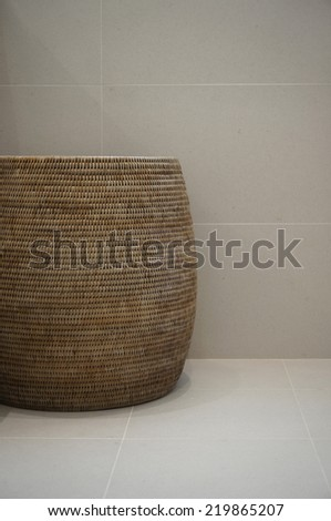 Rattan basket on a background of minimalistic grey tiles. - stock photo