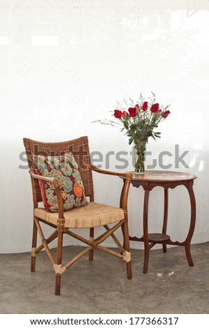 Rattan chair with colored pillow in a bright setting  - stock photo